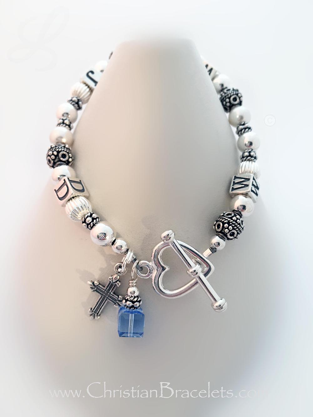 CB- WWJD-1S  WWJD Bracelet is shown with 3 add-ons...  They upgraded to a Heart Toggle Clasp and added a December or Blue Topaz Birthstone Charm and a Fancy Cross Charm.